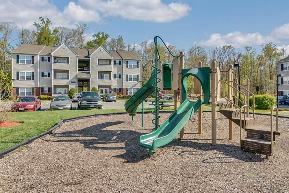 A children's playground with a large grass lawn at Creekpointe in Midlothian, Virginia