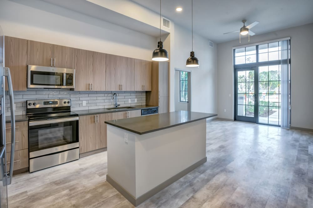 Kitchen with large island and floor to ceiling windows at The District Flats in West Palm Beach, Florida