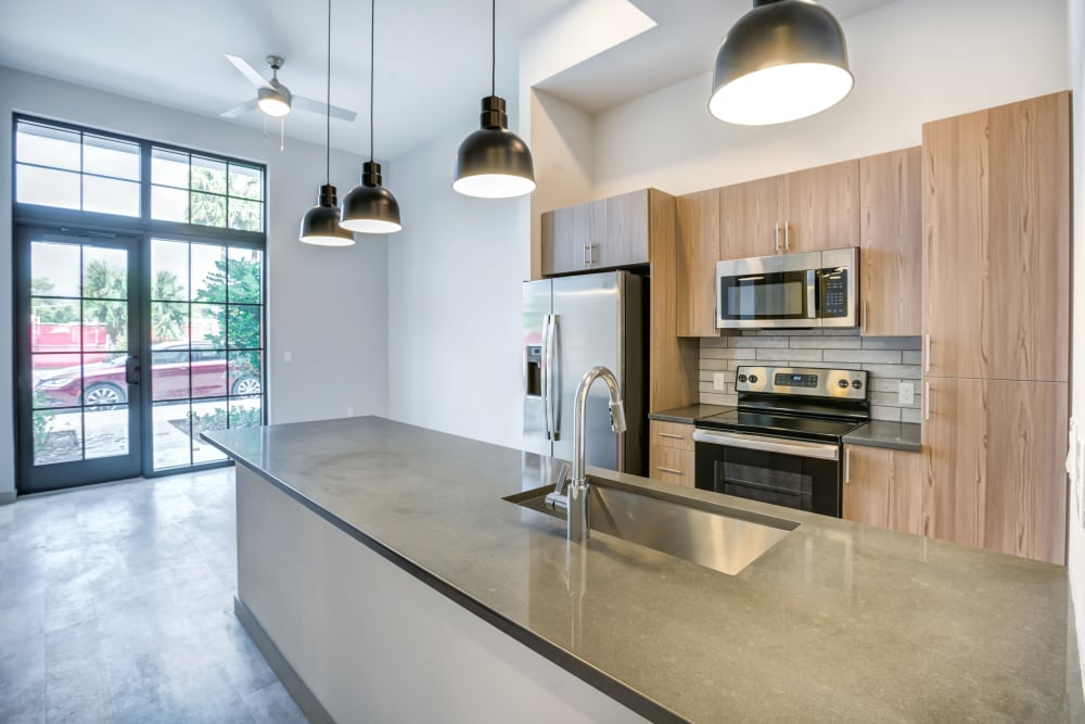 Kitchen with large island and overhead lighting at The District Flats in West Palm Beach, Florida