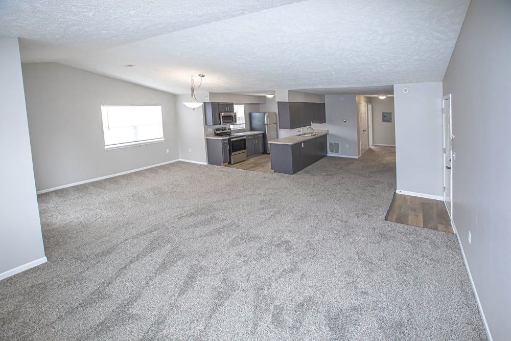 A large living room with plush carpeting at Silver Lake Hills in Fenton, Michigan