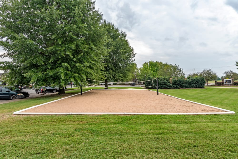 A sandy volleyball court surrounded by lush grass at Green Wood in Gallatin, Tennessee