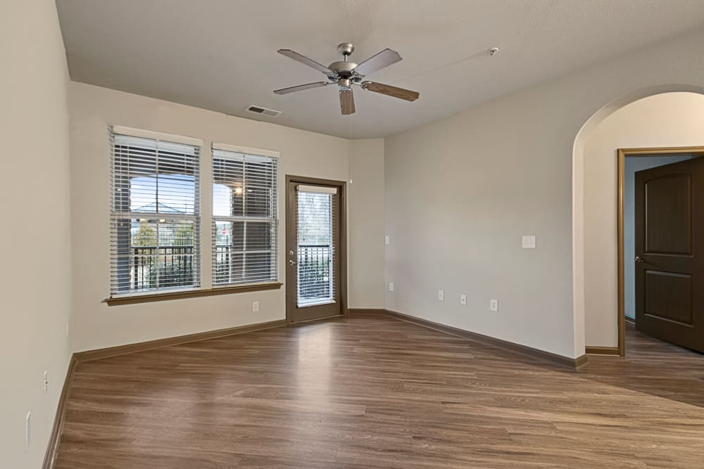 Large living room with wood flooring and a ceiling fan at The Addison at South Tryon in Charlotte, North Carolina