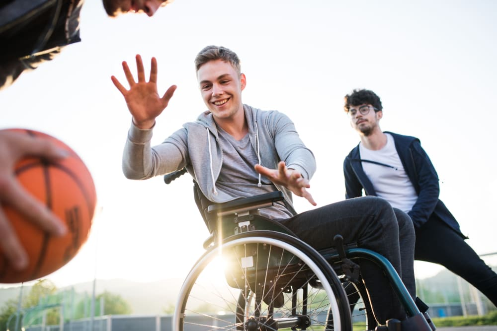 Student in wheelchair playing basketball with friends at Ikon Athens in Athens, Georgia