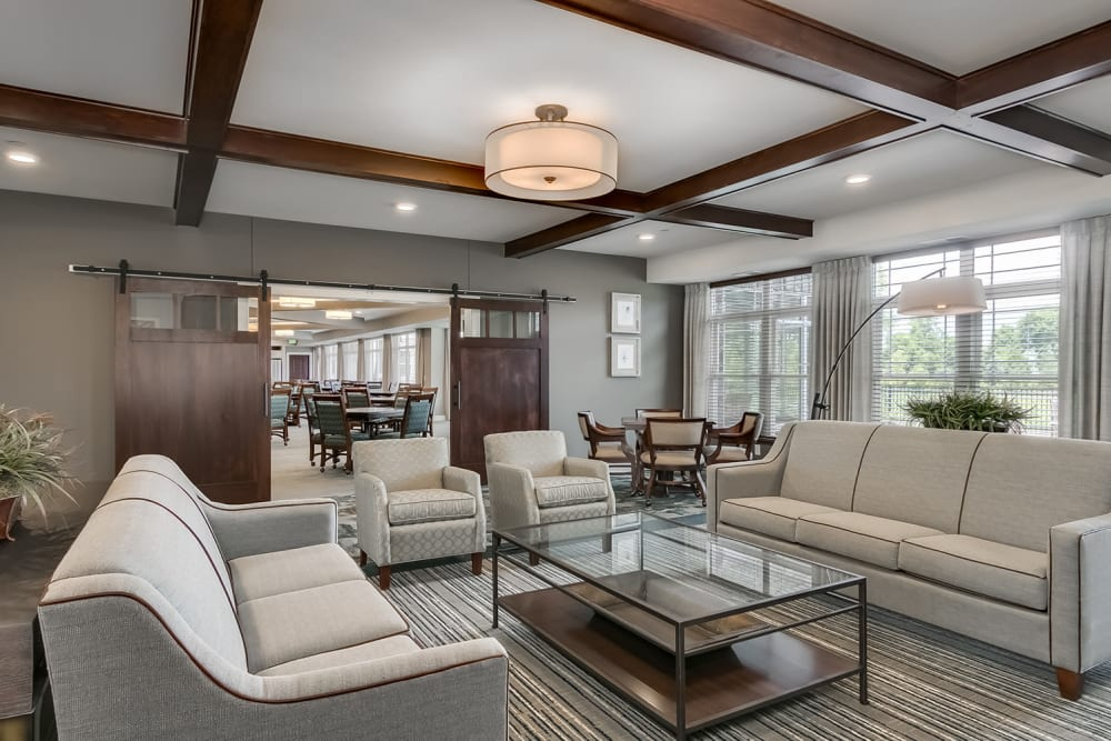 Lounge with large windows at Applewood Pointe of Westminster in Westminster, Colorado.