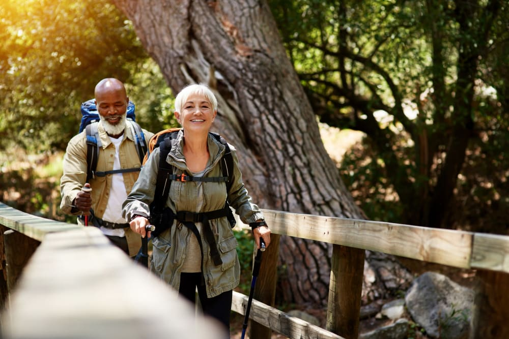 Two residents hiking and crossing a bridge on a trail near Applewood Pointe of Westminster in Westminster, Colorado