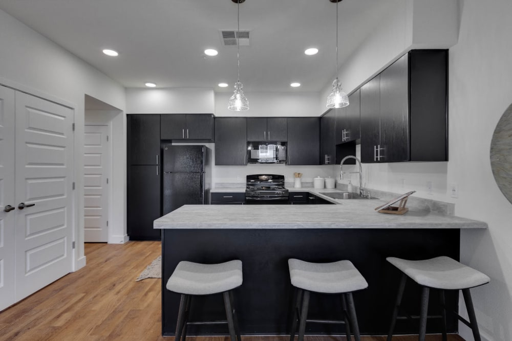 Island with quartz countertop and hardwood-inspired flooring in a model home's kitchen at Olympus Rodeo in Santa Fe, New Mexico