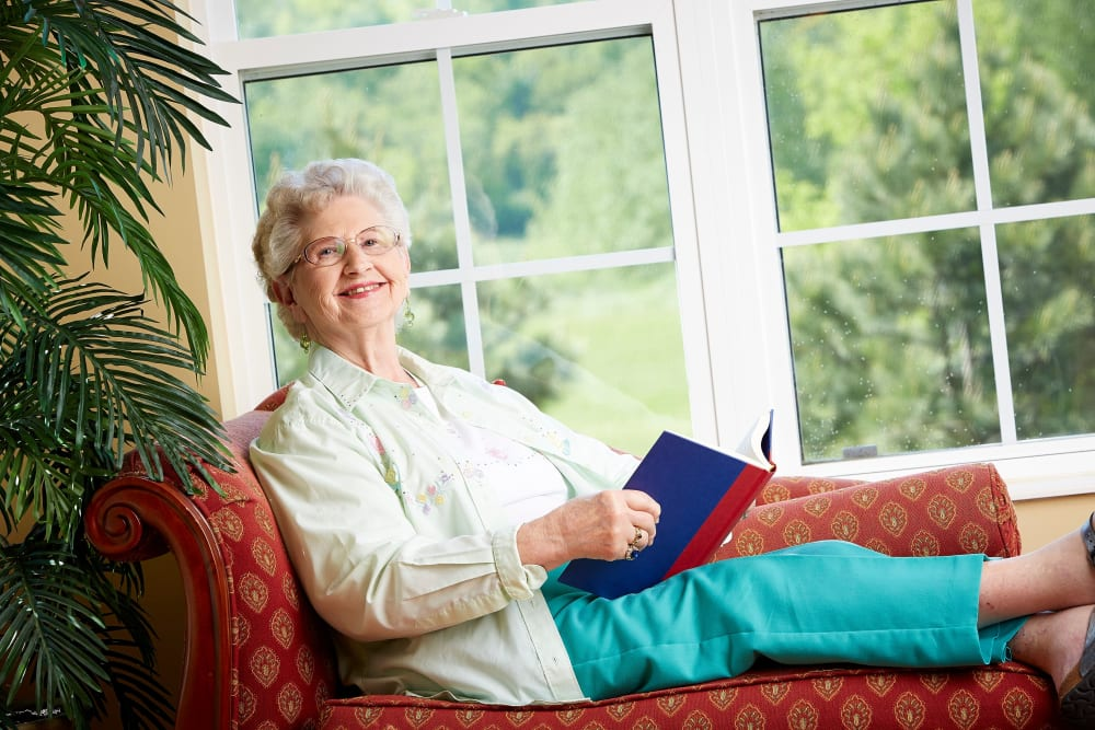 Resident enjoying a book by the window at Deer Crest Senior Living in Red Wing, Minnesota