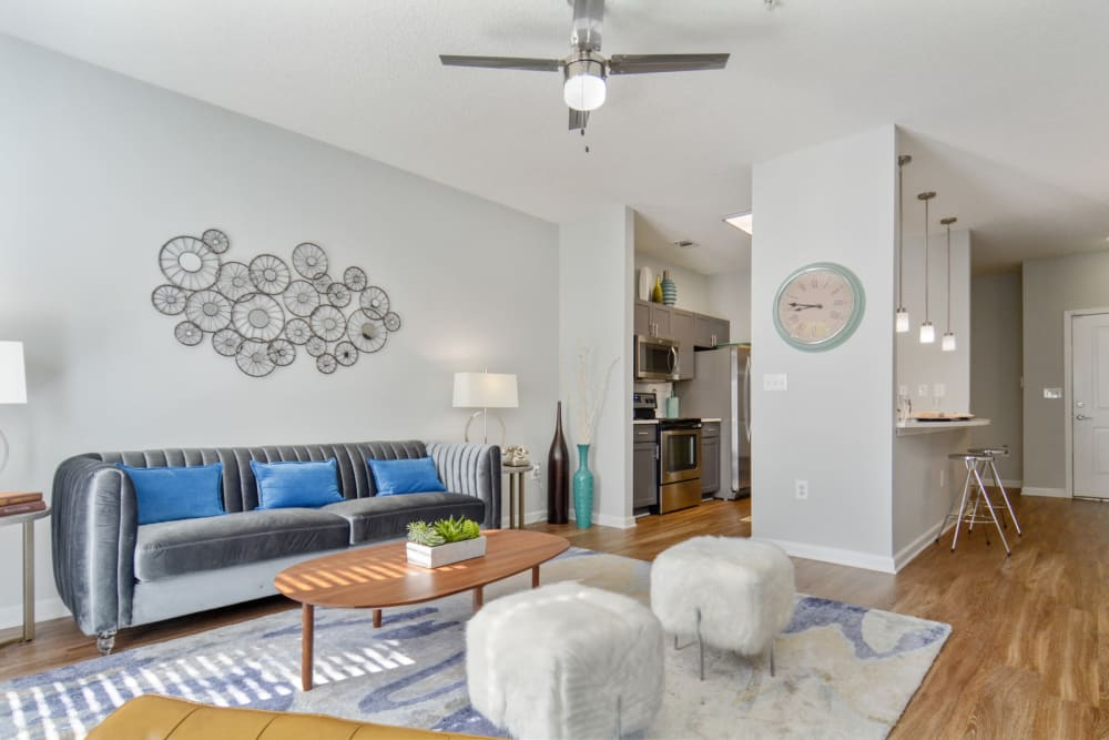 Model home's well-furnished living space with a ceiling fan and hardwood floors at Ellington Midtown in Atlanta, Georgia