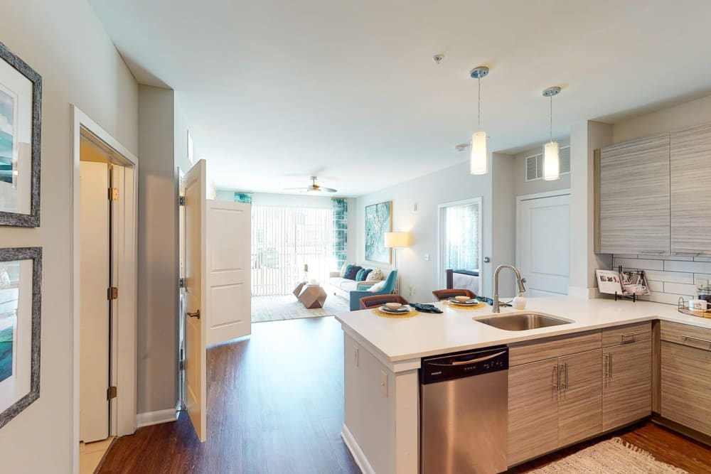 Model kitchen with living room view at The Palmer in Charlotte, North Carolina