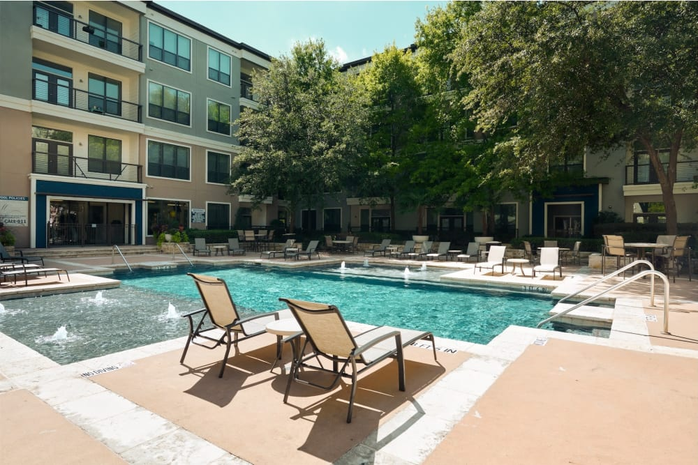 Beautiful resort style swimming pool surrounded by lounge chairs at Seville Uptown in Dallas, Texas