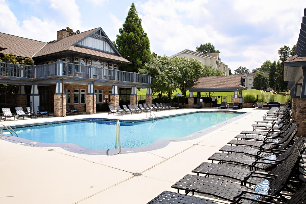 A swimming pool with a large sundeck and plenty of chairs at 7029 West in Greensboro, North Carolina