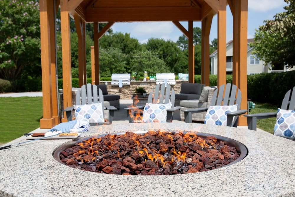 An outdoor firepit surround by lounge chairs at 7029 West in Greensboro, North Carolina
