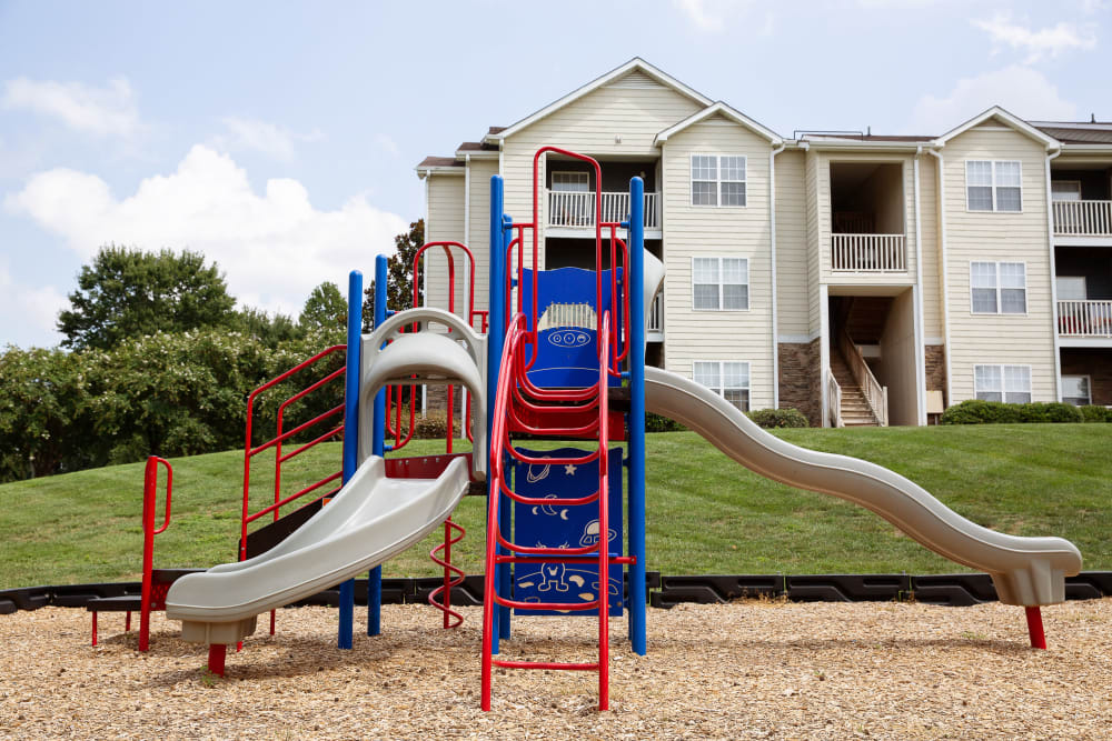 A children's playground with two slides next to a large grassy field at 7029 West in Greensboro, North Carolina