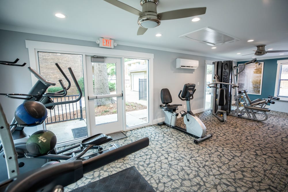 A fitness center with a ceiling fan at Mill Creek Flats in Winston Salem, North Carolina