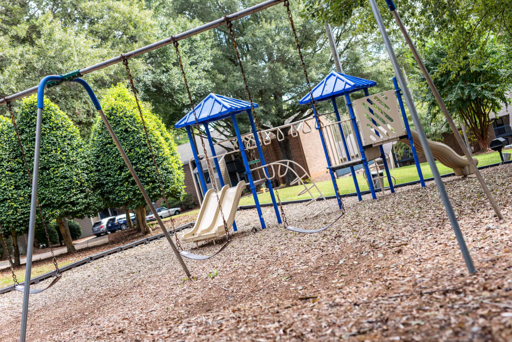 A children's playground with swings at Mill Creek Flats in Winston Salem, North Carolina