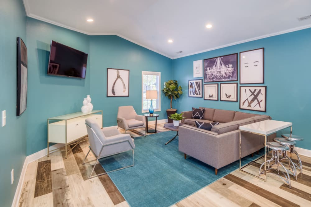 A clubhouse with comfortable seating and a flat-screen TV at Residences at West Mint in Mint Hill, North Carolina