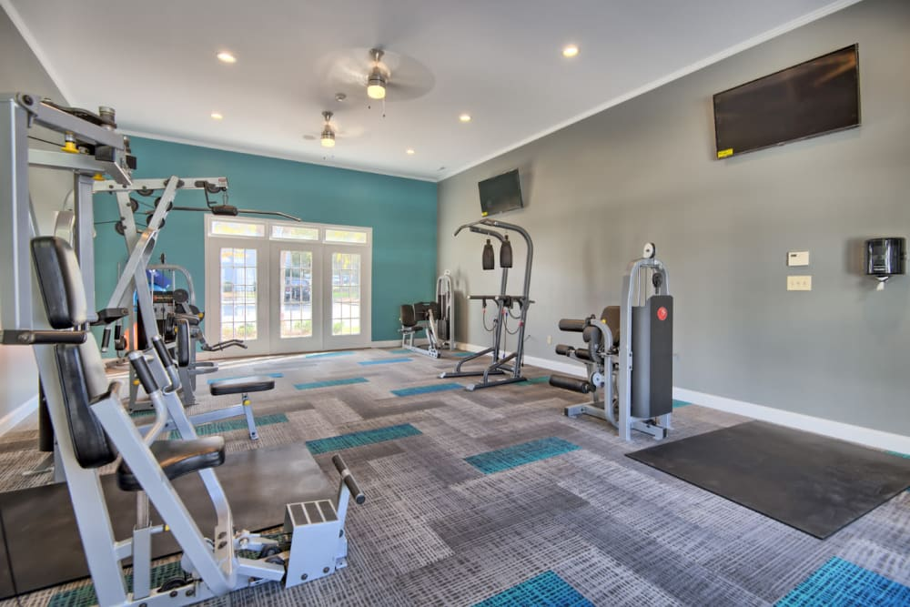 A fitness center with individual workout stations and a ceiling fan at Residences at West Mint in Mint Hill, North Carolina