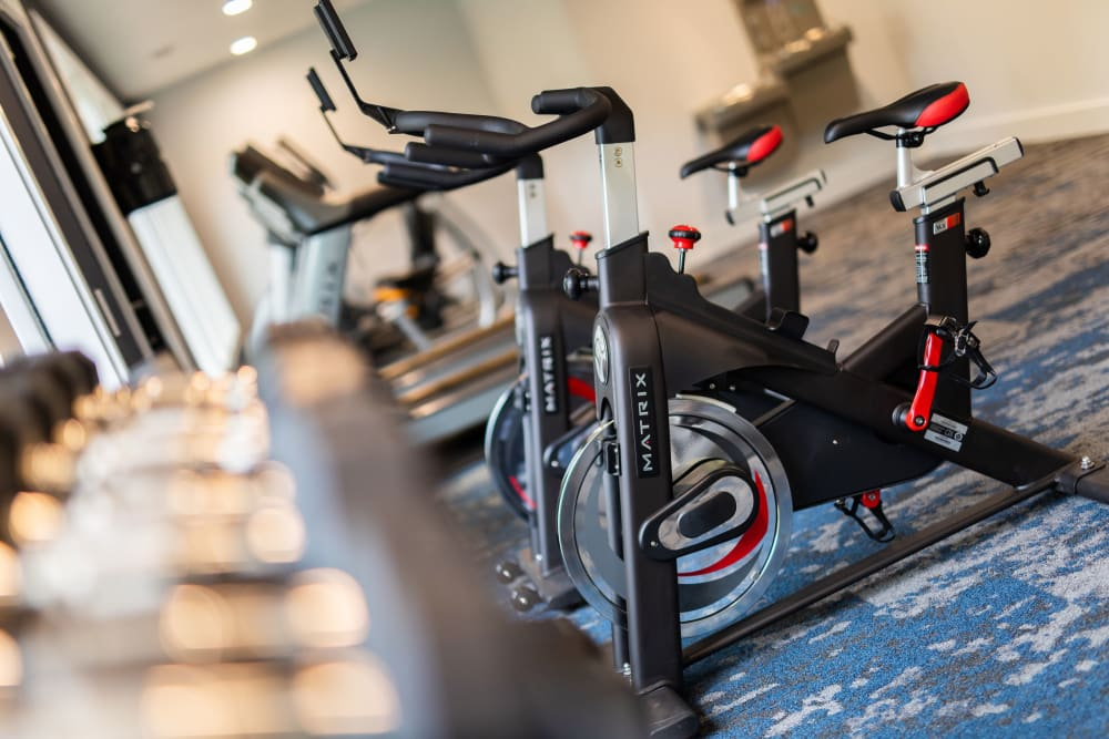 A fitness center with spin bikes and weight racks at The Corners at Crystal Lake in Winston Salem, North Carolina