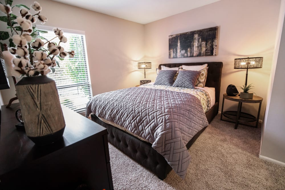 A bedroom with a large window and plush carpeting at The Corners at Crystal Lake in Winston Salem, North Carolina