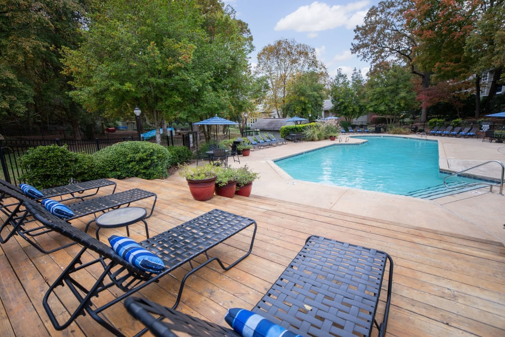 A swimming pool with a sundeck and lounge chairs at The Corners at Crystal Lake in Winston Salem, North Carolina