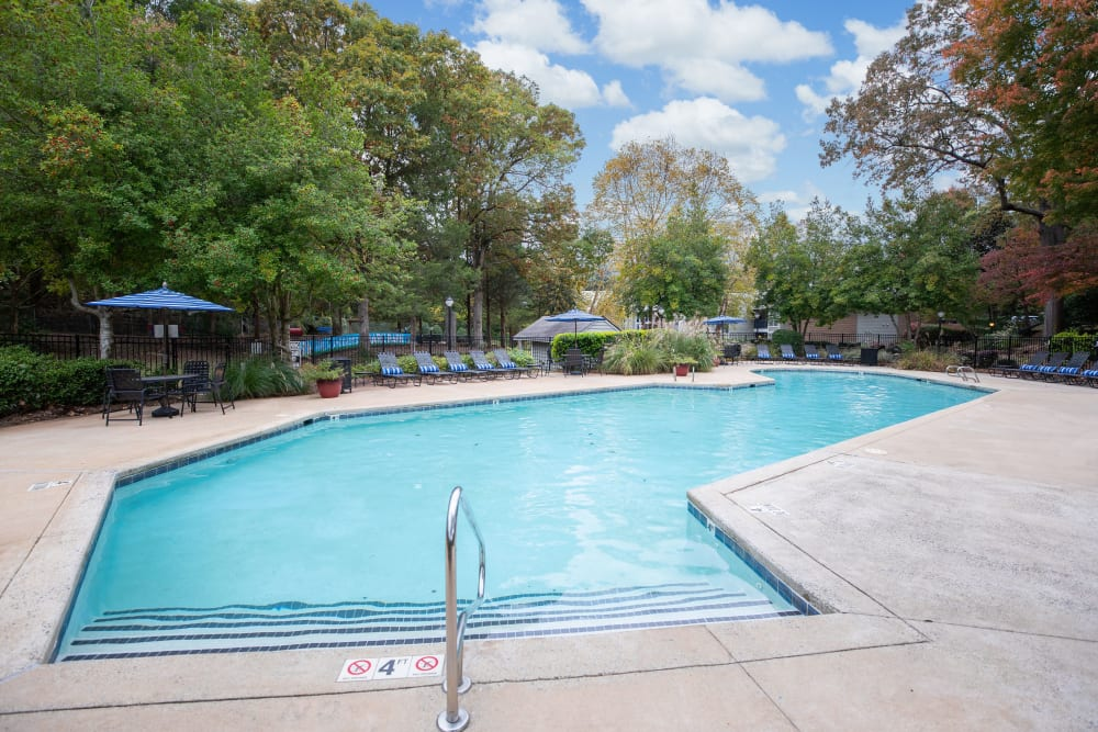 A large swimming pool surround by large lush trees at The Corners at Crystal Lake in Winston Salem, North Carolina