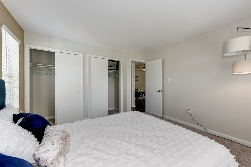 A main bedroom with a walk-in closet and bathroom at The Landings I & II Apartments in Alexandria, Virginia