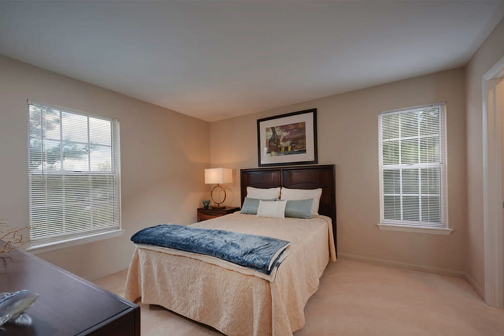 A large bedroom with windows and plush carpeting at The Landings I & II Apartments in Alexandria, Virginia