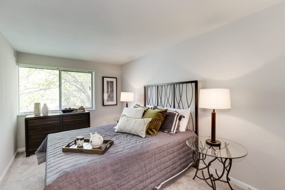 A bedroom with a large window at The Landings I & II Apartments in Alexandria, Virginia