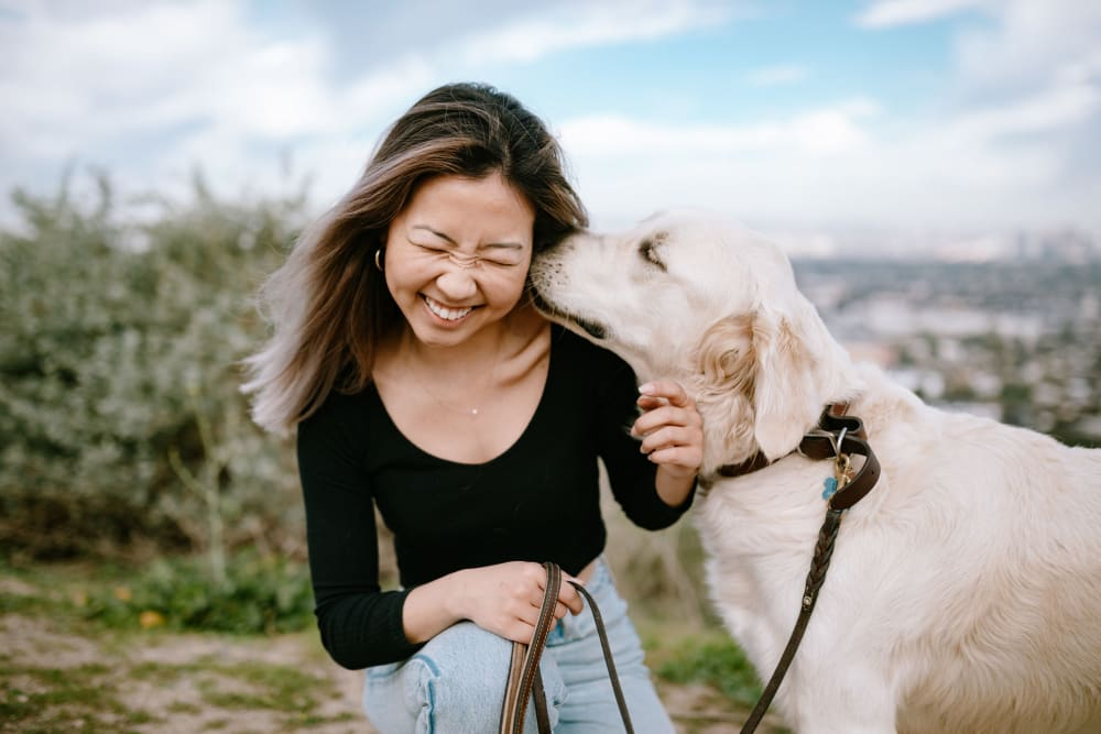Happy resident with dog at Vineyard Apartments in Ceres, California
