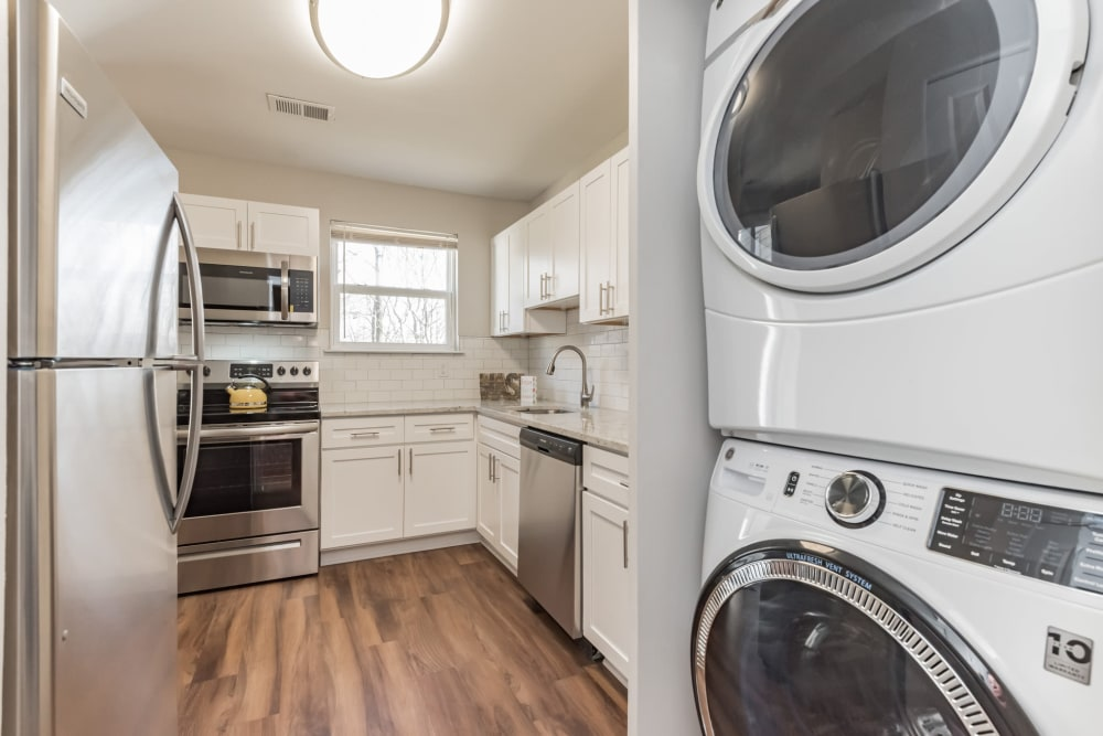 An upgraded apartment kitchen with a stacked washer and dryer at The Springs in Parkville, Maryland