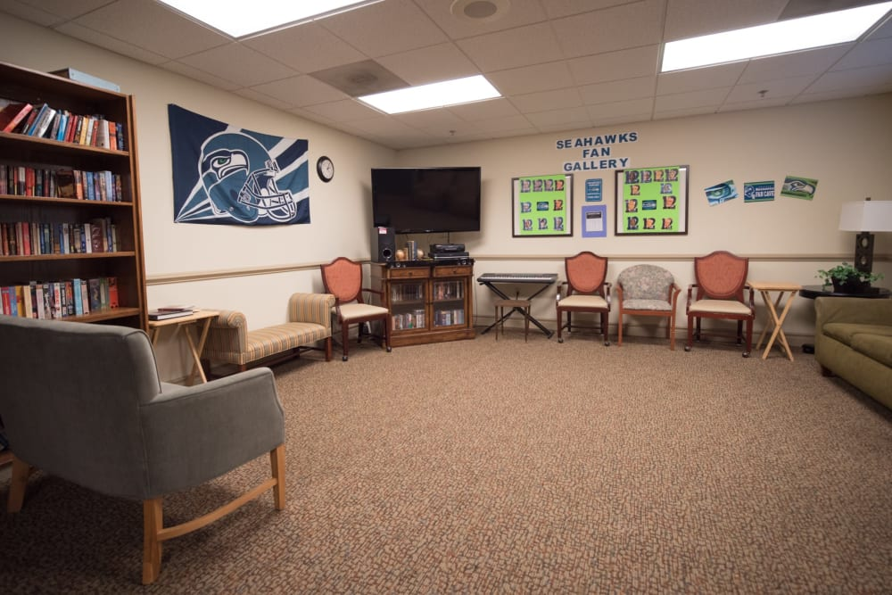 Community gathering space with book shelves and couches at Kenmore Senior Living in Kenmore, Washington