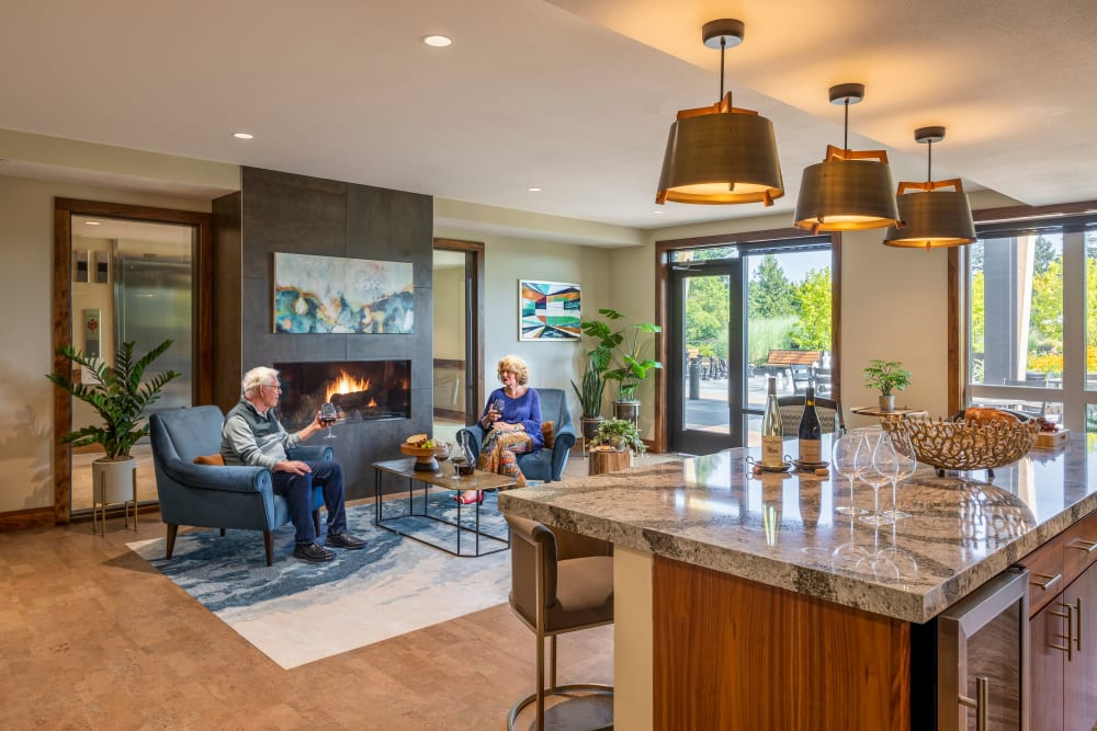 Resident in their apartment drinking wine at The Springs at Lake Oswego in Lake Oswego, Oregon