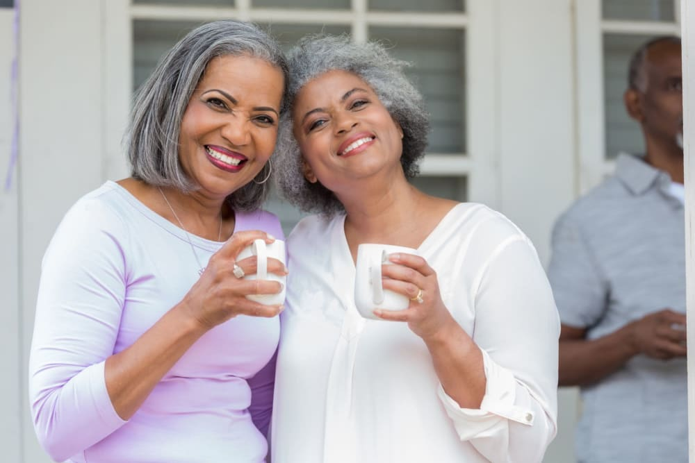 Two friends having a cup of coffee posing for a photo at Leisure Manor Senior Living in Sacramento, California
