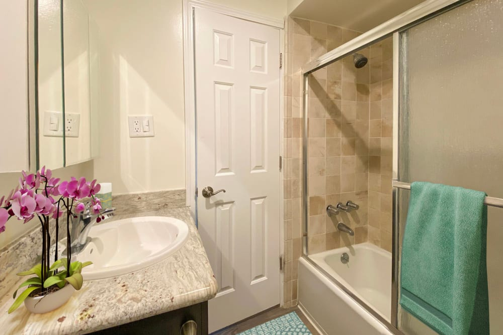 Granite countertop and a tiled shower in a model apartment's bathroom at Mediterranean Village in West Hollywood, California