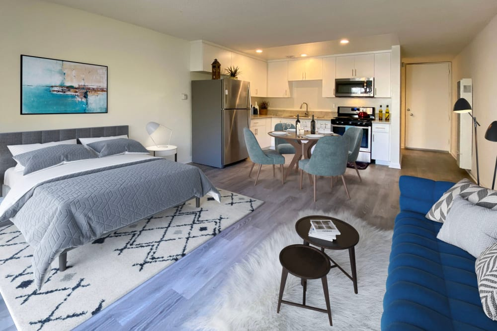Well-furnished studio apartment's living area with beautiful wood-style flooring at Mediterranean Village in West Hollywood, California