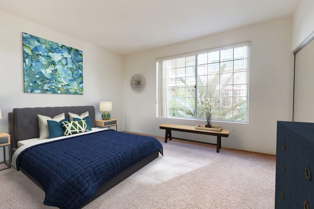 Plush carpeting and large bay windows flooding the room with natural light in a model home's primary suite at L'Estancia in Studio City, California