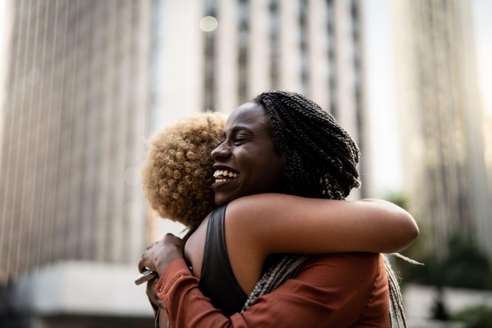 Two friends hugging each other out in the neighborhood near Vidorra McKinney Avenue in Dallas, Texas