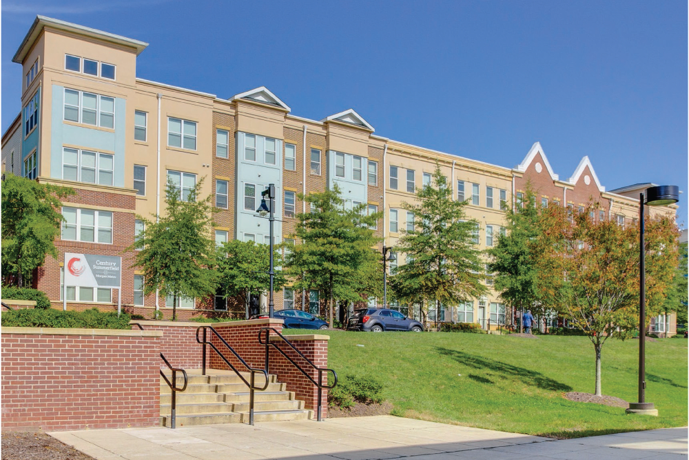 Exterior building with parking lot and green grass area at Summerfield at Morgan Metro in Landover, Maryland