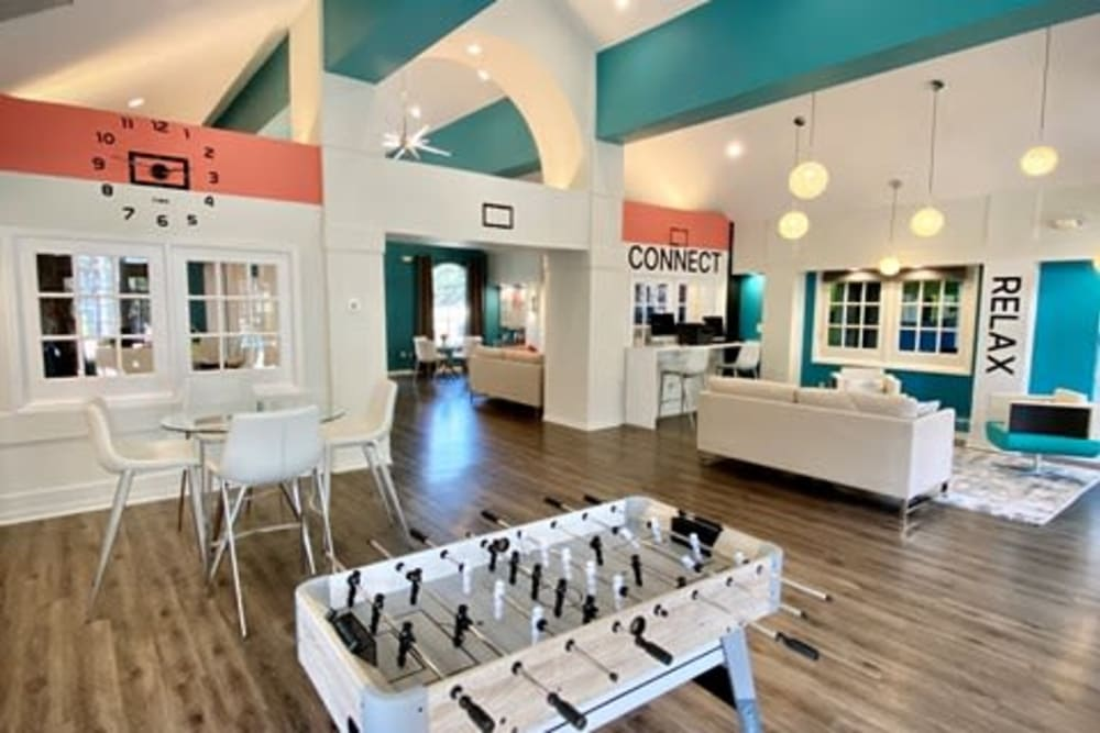 Game room with a foosball table and more in the resident clubhouse at 1801 MetroWest in Orlando, Florida