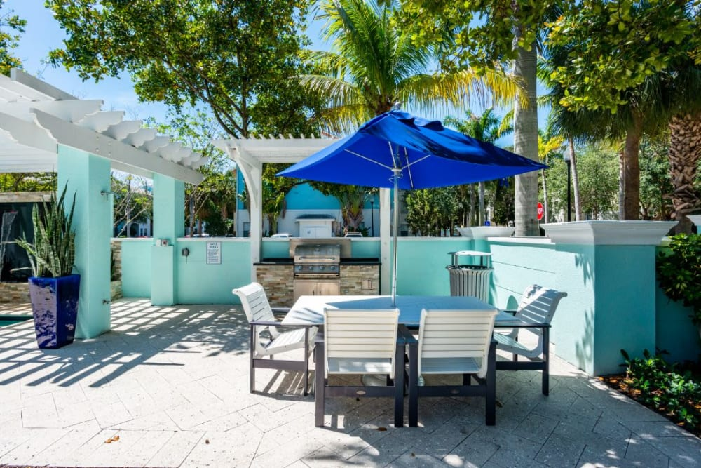 Bbq grilling area next to the pool with tables to sit and eat at, at The Pearl in Ft Lauderdale, Florida
