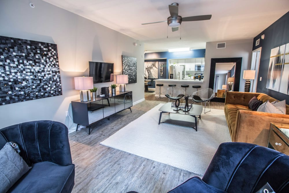 Incredibly spacious living room area with a ceiling fan and area rug over the wood flooring at The Pearl in Ft Lauderdale, Florida