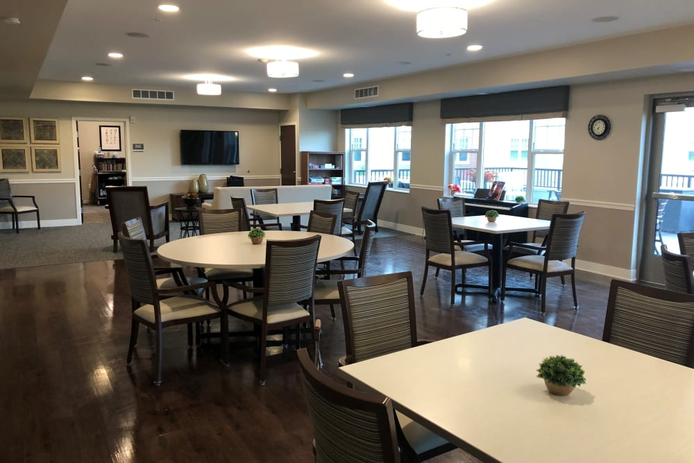Dining room with round tables at The Sanctuary at Brooklyn Center property, part of the Ebenezer Senior Living portfolio