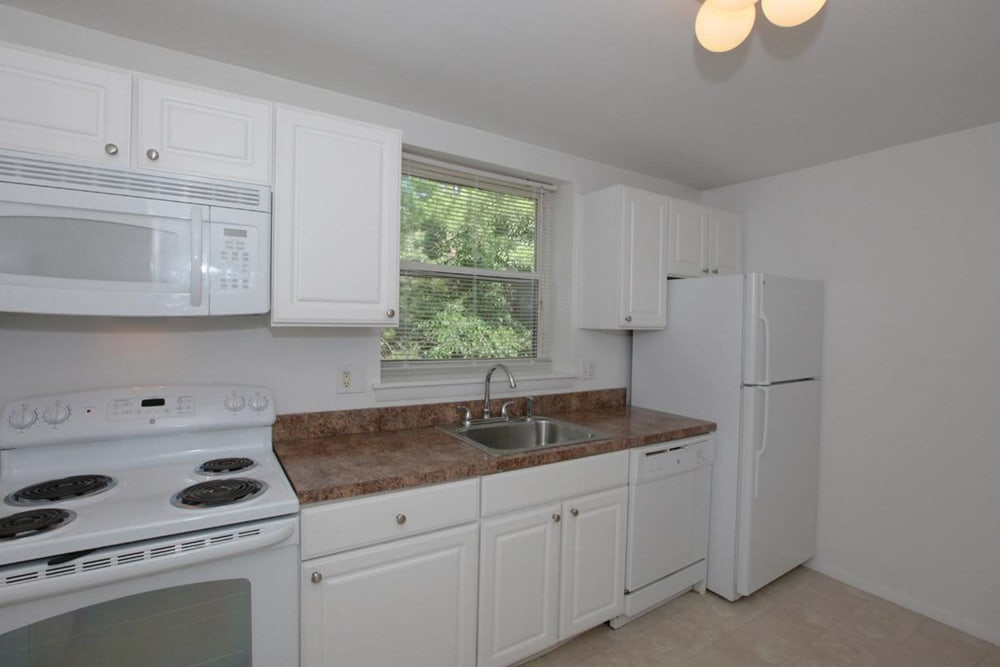 White cabinets in the kitchen with matching white appliances for an easy clean at Eagle Rock Apartments at West Hartford in West Hartford, Connecticut