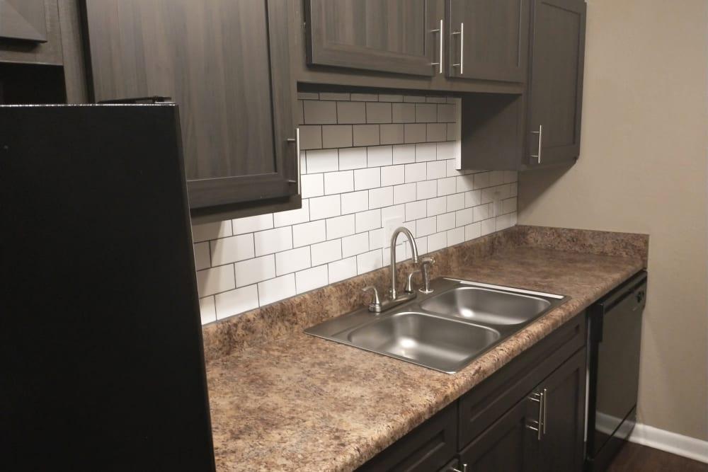 Black fridge, dark cabinets with white subway tile backsplash at The Village at Crestview in Madison, Tennessee