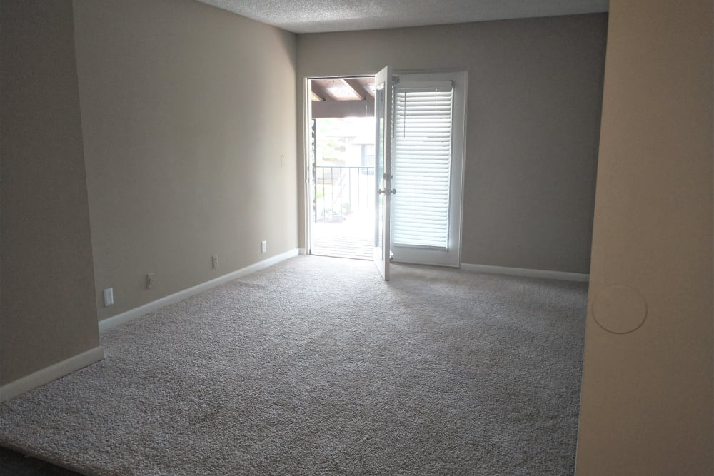 Plush carpet living room with door to patio/balcony at The Village at Crestview in Madison, Tennessee