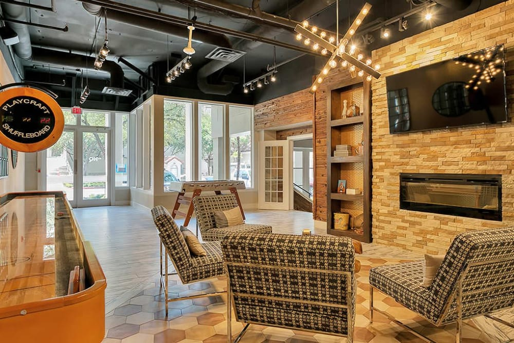 Community room with shuffle board at Alesio Urban Center in Irving, Texas