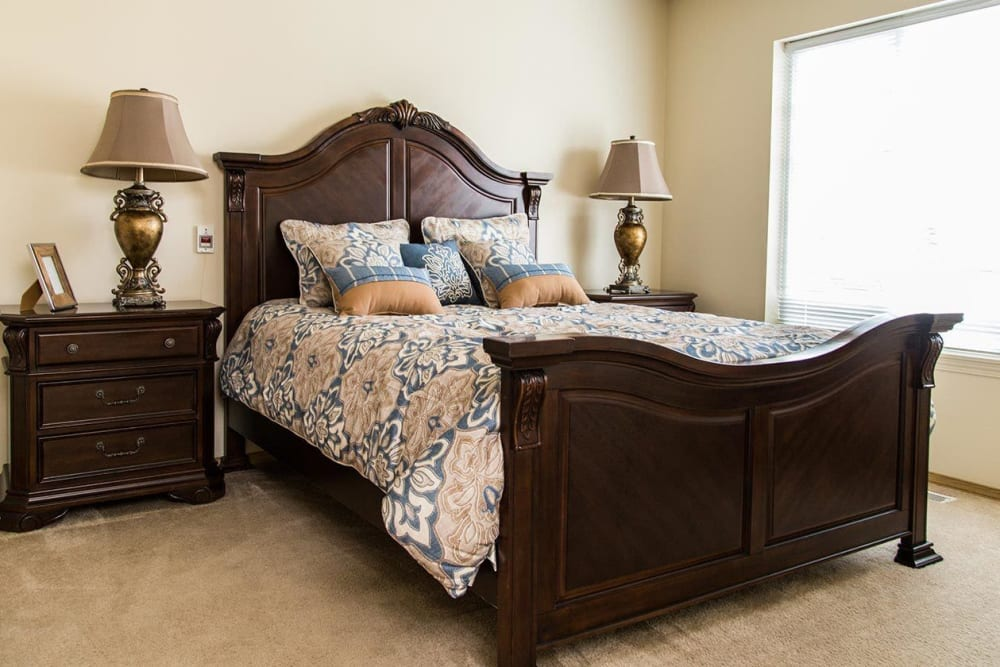 Bedroom with luxurious woods accents at upscale senior living facility at The Springs at Butte in Butte, Montana