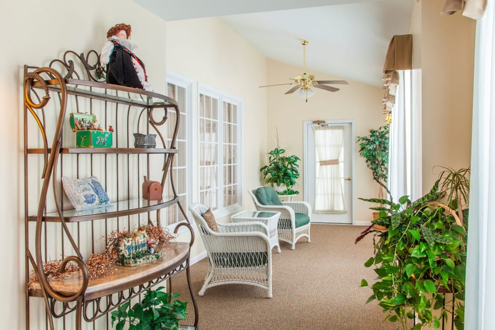 Charming sunroom complete with seating at Grand Victorian of Rockford in Rockford, Illinois