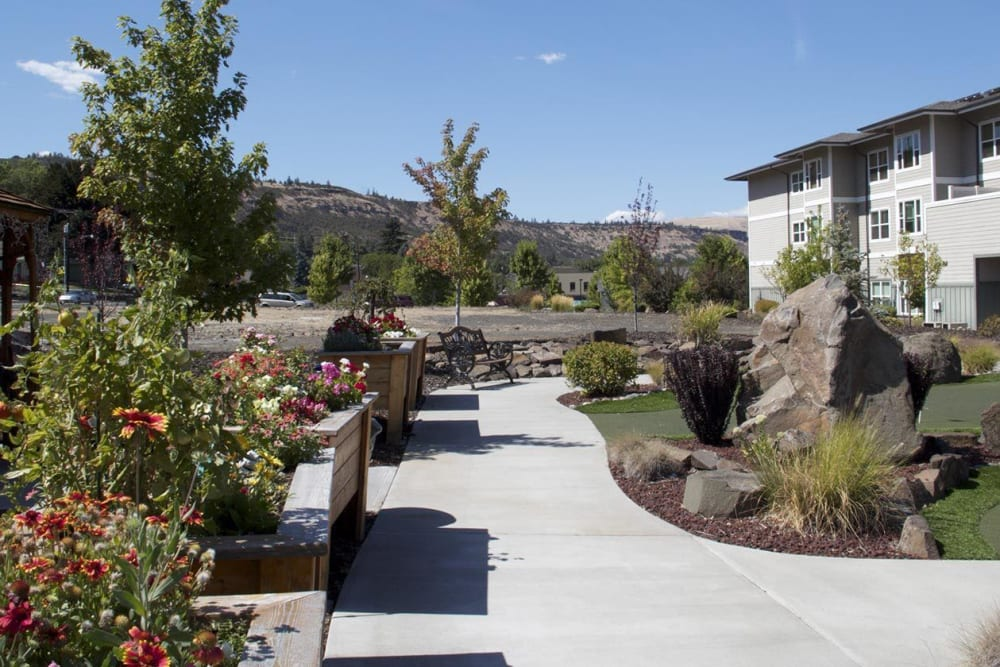 Sunny and inviting walk up to upscale senior living facility complete with fushia flowers at The Springs at Mill Creek in The Dalles, Oregon