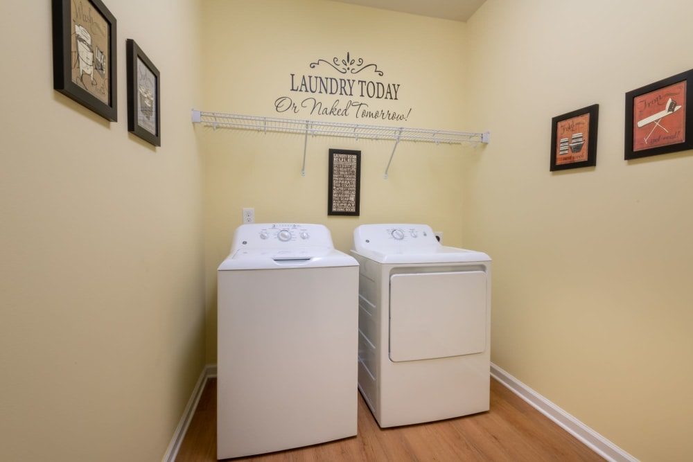 Laundry machines in unit with storage space above at The Reserve at White Oak in Garner, North Carolina